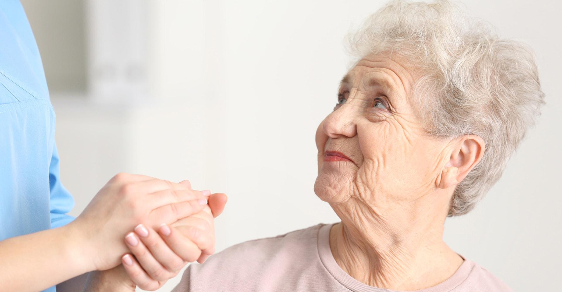 Altenpflegehelferin hält die Hand einer älteren Dame in der ToP GbR Pflegeschule