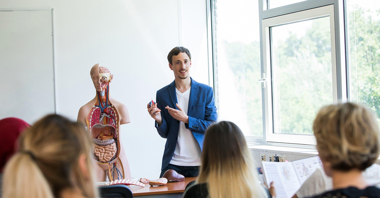 Lehrer der Pflegeschule ToP GbR unterrichtet einen Klassenraum mit Auszubildenden