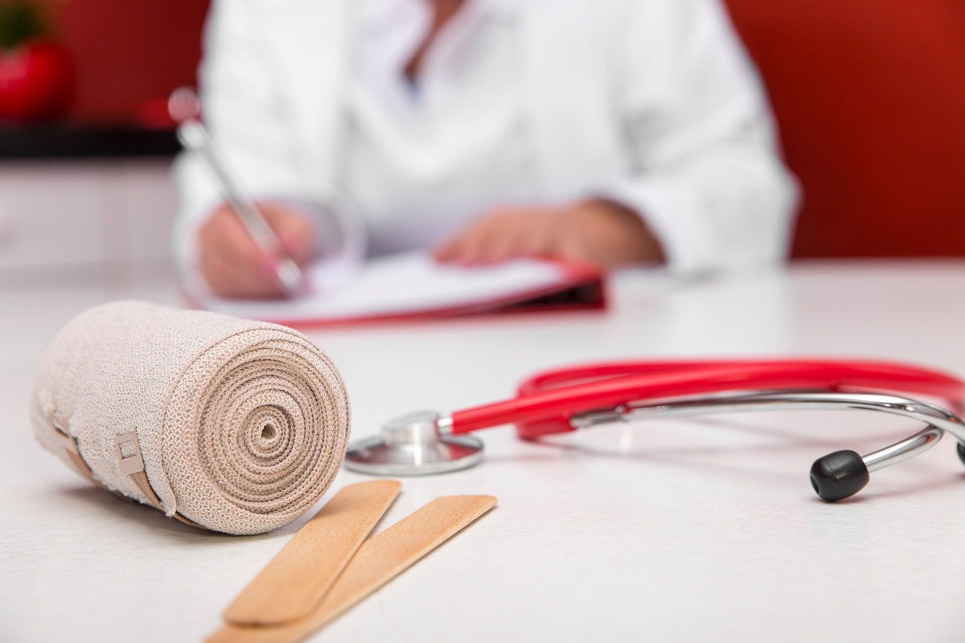 Ärztin am Tisch mit Bandage und anderen Utensilien zur Pflegeschule der ToP GbR